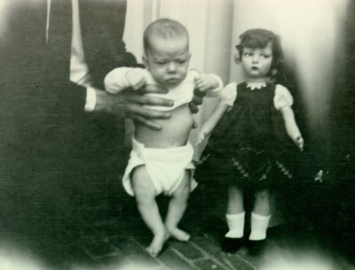 Linus Pauling holding baby Peter Pauling next to a life-size doll.Picture. 1931