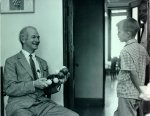 Linus Pauling showing a molecular model to a young boy.