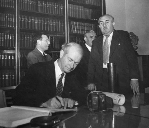 Linus Pauling signing the guest registry at the Weizmann Institute of Science library.