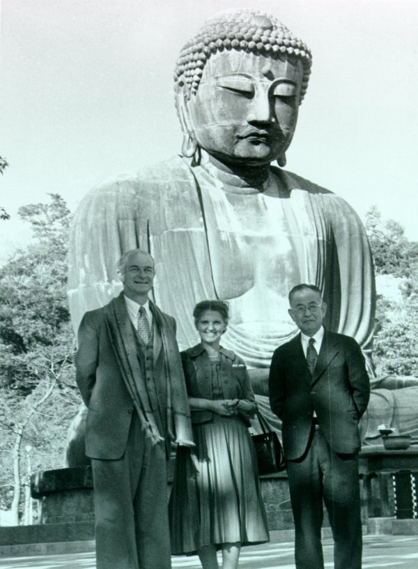 Linus Pauling, Ava Helen Pauling and Professor San-ichiro Mizushima standing in front of a large statue of the Buddha. Picture.