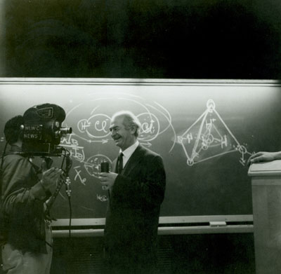 Linus Pauling speaking to a television cameraman, Ohio State University Medical School. Picture. March 1962