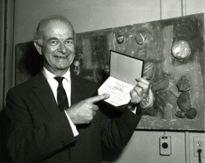 Linus Pauling displaying his honorary high school diploma, conferred by Washington High School, Portland, Oregon. Picture. 1962