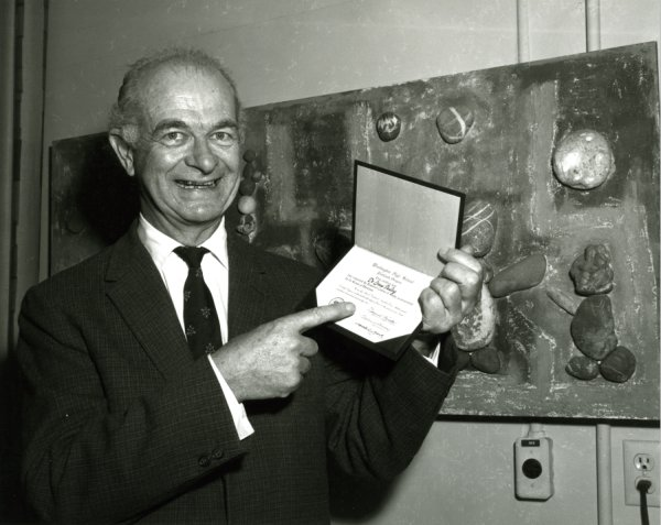 Linus Pauling displaying his honorary high school diploma, conferred by Washington High School, Portland, Oregon.Picture. 1962