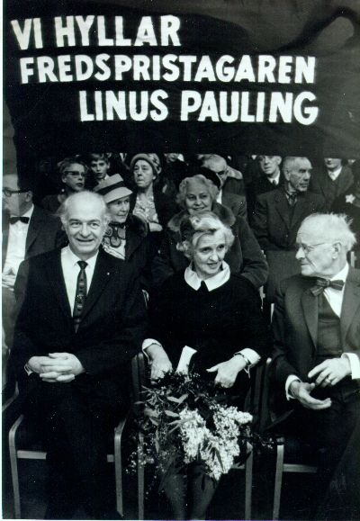 """Linus and Ava Helen Pauling with sign """"Vi Hyllar Fredspristagaren Linus Pauling."""" Gothenburg, Sweden.Picture. 1963"""