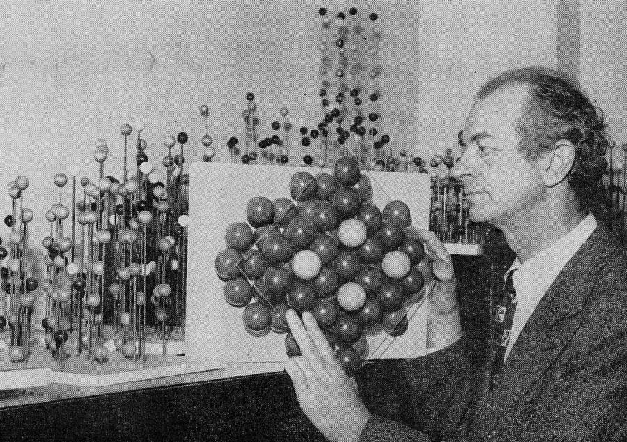 Linus Pauling holding a molecular model depicting the atomic arrangement of metallic alloys.