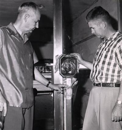 Ed Allworth (left) examining a Beaver door handle at the Memorial Union. Ca. 1950s.