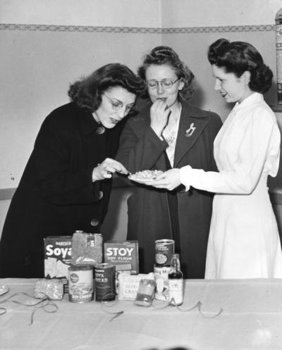 Mary Louise Armstrong (on right) offering a taste of soy foods to two other women, circa 1945. Rainier Vista Cooking School.
