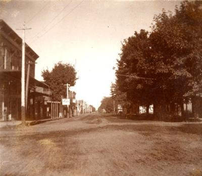 Second street, looking north, before it was paved, ca. 1900. A trolley in the middle of the street is visible in the distance.