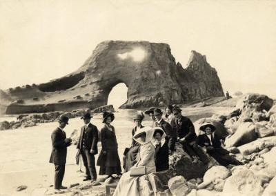 College students on Nye Beach in Newport, Oregon, May 1910. The woman in black sitting on the rock at front of photo is Ethel Allen. Ruby Elliott is the woman seen between the two men at the back of the group of students.