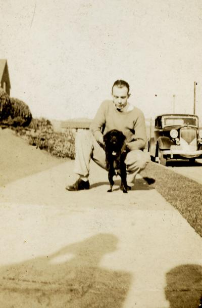 Robert Crookham playing with a dog, ca. 1930s.