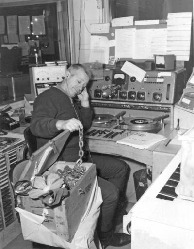 Barney Keep posing with a box of chains, ca. 1960s. Keep worked with KOAC before becoming a famous radio personality for Portland's KEX radio station from 1944-1979.