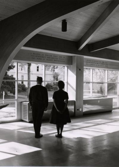"<p>Unidentified individuals standing in the Memorial Union Commons, ca. 1960s. The wall that they face reads ""I believe in Oregon State and in her democracy and her far reaching bond of beaver brotherhood. I believe in Oregon</p><p>				State - and since she has accepted me as a beaver I too am a guardian of beaver spirit.""</p>"