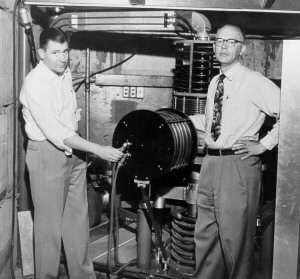 Physicists David Nicodemus and Richard Dempster posing with the college's cyclotron, ca. 1954.