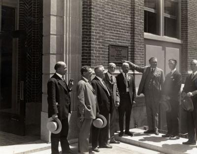 <p>Pharmacy Building dedication, July 1925. Pictured from left to right: E. L. Necomb, F. R. Peterson, Frank S. Ward, William F. Woodward, Pharmacy Dean Adolph Ziefle, A. E. Cosby, H. S. Noel, J. K. Weatherford. Components of</p><p>				the OSC Clippings scrapbooks are believed to have been assembled by Adolph Ziefle.</p>