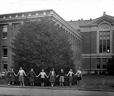 Coeds encircling the giant holly tree behind what is now Kidder Hall, December 1940. The women pictured were members of the Theta Sigma Phi national women's honor society in journalism.