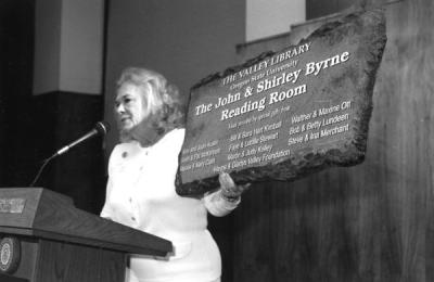 Joan Austin holding a sign for the Valley Library's John and Shirley Byrne Reading Room, a gift given to Byrne, OSU President, upon his retirement. March 1996.