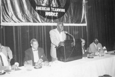 Baseball great Jackie Robinson, speaking at an Urban League of Portland meeting, 1955. Edwin C. Berry, Director of the Urban League, is seated second from left.