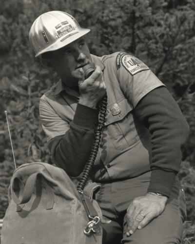 A United States Forest Service Ranger using a portable radio.