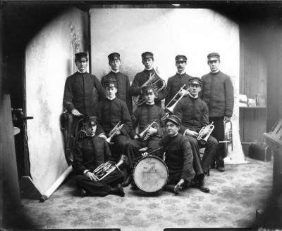 The OAC Band, ca. 1899, posing with the Corvallis High School drum. The drum is illustrated with a drawing of the Battleship Oregon.