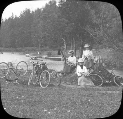 Women bicyclists sitting with flower bouquets, circa early 1900s.