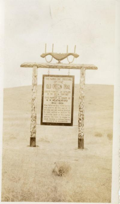 "Old Oregon trail marker, ca 1920s. Sign reads: ""This marks the crossing of the Old Oregon Trail used by pioneers and settlers of the Oregon Territory. This marker in honor of W. W. Weatherford, 1844-1926. Who followed this route across the plains at the age of 17, driving oxen and walking barefoot. He later settled on Shuttler Flat, five miles south of this marker, and was the first to engage in wheat farming in Gilliam County. Erected by M. Weatherford."""