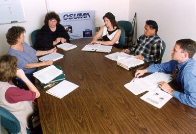 OSU Management Association Board Meeting, 1999. OSUMA members (pictured from left to right) Tammy Kreig, Beth Rietveld, Debbie Jimmerson, Laurel Busse, Gideon Alegado, and Chad Klaus consider new ways to connect OSU professional staff to resources in the university community and elsewhere.