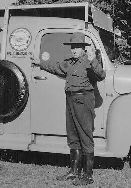 Conservationist Bill Schaeffer pointing to the Oregon Wildlife Federation emblem on the OWF public relations car, ca. 1960.