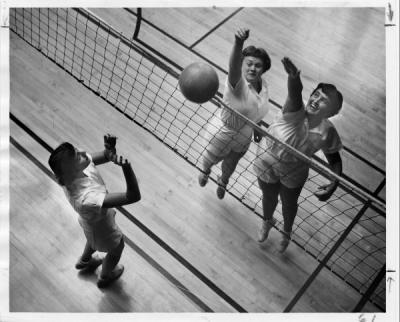 Unidentified women playing volleyball, ca. 1950s.