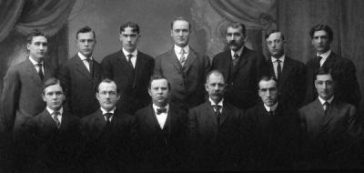 Group photo of the School of Engineering and Mechanic Arts Faculty, 1909. Front row (L to R): Willibald Weniger; Thomas Mooney Gardner; Gordon V. Skelton; Grant Albert Covell; Henry M. Parks; and Mark Clyde Phillips. Back row (L to R): C. L. Knopf; Earl Vincent Hawley; Samuel Herman Graf; E. P. Jackson; William McCaully Porter; Herbert Edward Cooke; and Wilford W. Gardner.