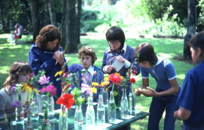Several 4-H youth gathered around a table participating in the flower identification contest, 1975.