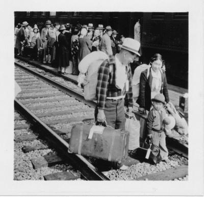 A Japanese family with their luggage, preparing to board an evacuation train, Hood River, Oregon, 1942.