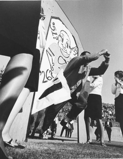 "Dee Andros (the Great Pumpkin) leading the football team onto the field before the Homecoming game against Idaho, 1966. Andros was the Oregon State Head Coach for football from 1965-1975, and Athletic Director from 1975-1985. In 1967 Andros lead the OSU ""Giant Killers"" team to two victories and one tie against the top three teams in the country: USC, Purdue and UCLA."