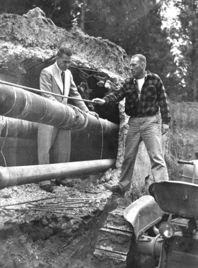 Otto Meyer of the OSC physical plant (left) and V.A. Stanford of Donald Drake Construction in Portland (right) manipulating a pipe being installed in a new campus heating tunnel, June 1951.