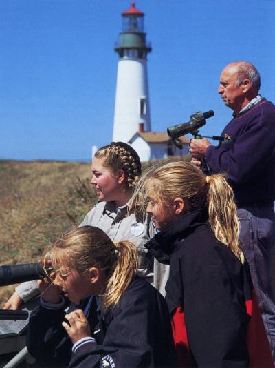 "Image from an article titled ""Job Shadows"" describing internship positions that OSU Fish and Wildlife majors have completed as part of their degree requirement. Caption reads: ""Nemesia Herzstein (center) points out sea life to visitors at the Yaquina Head Lighthouse and Interpretive Center. Herzstein interned with the Bureau of Land Management as a naturalist."""