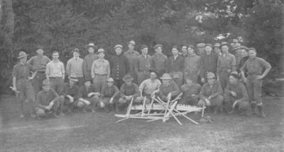 """The Foresters Ready for the Tall Timber,"" ca. 1912. Forestry professor George W. Peavy (kneeling, left) poses with members of the Forest Club. The club held two meetings a month, one of which was devoted to forestry issues and business matters of the club. The other was social, and occasionally took ""the form of a night's vigil in the forest, where, seated around the camp fire, stories are told and songs are sung, while the aromatic odor of camp coffee is wafted on the air, and 'overland trout' frizzles in the frying pan."""