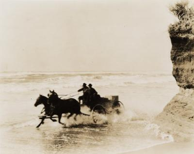 A wagon being driven through the surf on the Oregon coast, ca 1910s.
