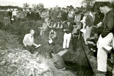 Art King, standing in ditch and wearing light colored jacket, addressing a group of students, 1967.