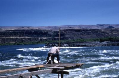 Man fishing on platform above Celilo Falls on the Columbia River, 1956
