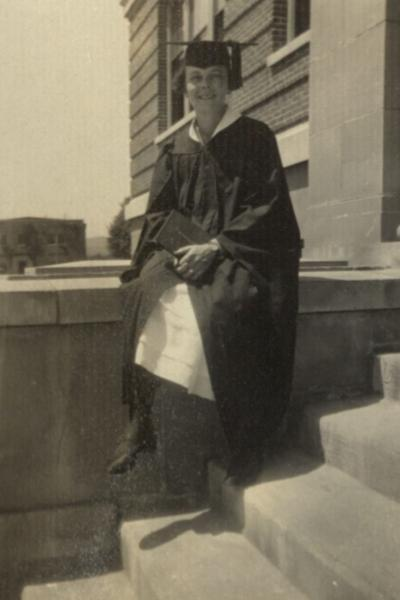 A woman, tentatively identified as Helen H. Marburger, in graduation cap and gown, 1925