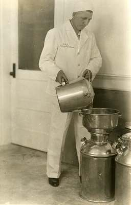 OSC Dairy Department Worker Pouring Milk, ca. 1935