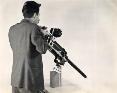 Black and white photographs of Roger Hayward demonstrating the use of a military machine gun.