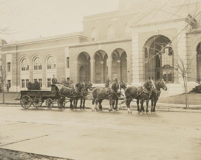 Clydesdales mounted to a wagon and standing adjacent to the Women's Building