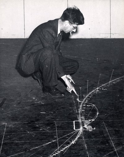 Black and white photograph of Roger Hayward tracing a trajectory on the floor.