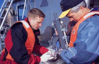 "<p>Image from an article titled ""Sheer Number"" by Carol Savonen. Photo caption reads: ""Morris, left, works with Giovannoni to remove water from a metal sampling canister they lowered into the Pacific Ocean. Back on the OSU</p><p>				campus, they'll try to isolate, reproduce and study microbes in the water sample to learn about their role in ocean ecosystems.""</p>"
