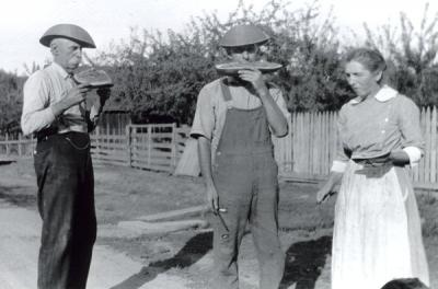 "Image from Marie Brady Farm folder annotated: ""John, Hilery, and Catherine Gilham standing in Old Pacific Hwy. 99 approx. 1920."""