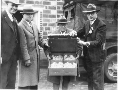 Men in front of the Russell Poultry Building showing baby chicks, ca. 1940s.