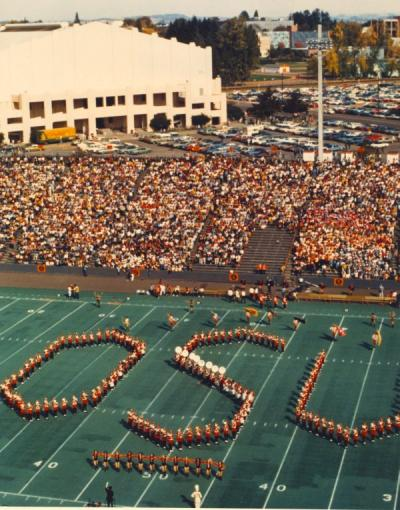The OSU Marching Band performing at halftime of the OSU-UCLA football game at Parker Stadium, 1972. Gill Coliseum is seen in the background.