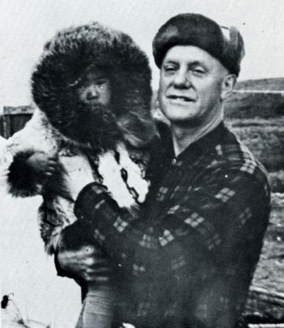 "Paul H. Jensen and an Alaskan Eskimo child. Image extracted from Jensen's publication ""Hunters of the Arctic Rim,"" circa 1960s."