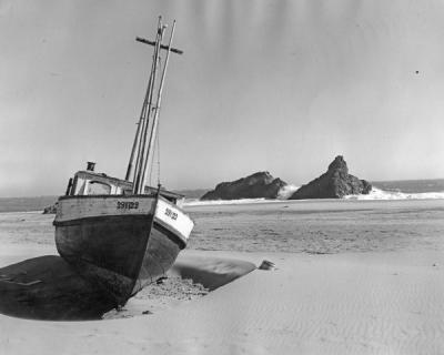 """Neptune's toll."" A wrecked fishing boat on the sand at Brookings, Oregon, ca. 1930s."