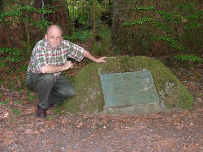 Gerald Williams posing with the Gifford Pinchot National Forest marker